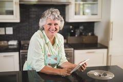 Portrait de la femme supérieure de sourire à l'aide du comprimé numérique sur le compteur dans la cuisine Photo stock