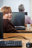 Portrait de la femme supérieure de sourire s'asseyant dans la classe d'ordinateur Photographie stock