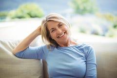 Portrait de la femme supérieure de sourire s'asseyant sur le sofa dans le salon Photos libres de droits