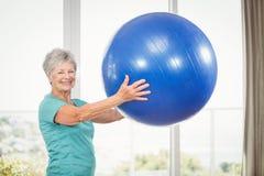Portrait de la femme supérieure de sourire tenant la boule d'exercice photo stock