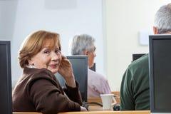 Portrait de la femme supérieure sûre s'asseyant dans la classe d'ordinateur Images stock