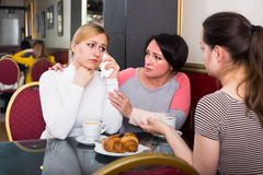 Portrait de la femme trois nerveuse s'asseyant dans le café Photo stock