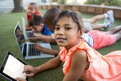 Portrait de la fille à l'aide du comprimé numérique au parc Images stock