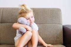 Portrait de la fille adorable émotive d'enfant en bas âge étreignant son jouet, ours de nounours et s'asseyant sur le sofa, d'int photos stock