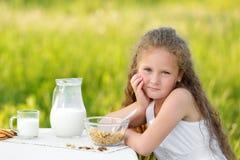 Portrait de la fille adorable ayant le petit déjeuner et le lait boisson extérieurs Céréale, mode de vie sain images stock