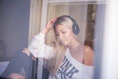 Portrait de la fille assez heureuse avec des écouteurs écoutant la musique pop Image libre de droits