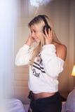 Portrait de la fille assez heureuse avec des écouteurs écoutant la musique pop Images libres de droits