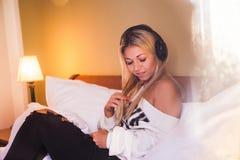 Portrait de la fille assez heureuse avec des écouteurs écoutant la musique rock Photos stock