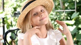 Portrait de la fille attirante blonde souriant, touchant ses cheveux avec un chapeau de paille dessus lifestyle concept d'enfance banque de vidéos