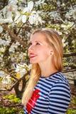 Portrait de la fille blonde de ressort se tenant dans le jardin de floraison Images libres de droits