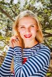 Portrait de la fille blonde de ressort se tenant extérieure dans le jardin de floraison Photo libre de droits