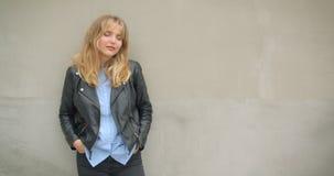 Portrait de la fille blonde fraîche dans la veste en cuir avec des mains dans des ses poches observant de côté rêveusement sur le banque de vidéos