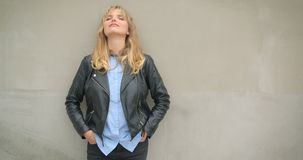 Portrait de la fille blonde fraîche dans la veste en cuir se penchant sur le mur gris observant de côté rêveusement dehors banque de vidéos