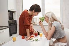 Portrait de la fille blonde mignonne tenant le salaire et parlant à son amie tandis qu'elle s'assied sur la table de cuisine et r Photo stock