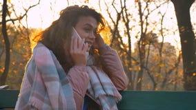 Portrait de la fille caucasienne aux cheveux bouclés s'asseyant sur le banc et parlant sur le téléphone portable attentivement en photo stock