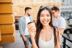 Portrait de la fille chinoise heureuse regardant sur l'appareil-photo et le sourire Elle tient une tasse de café dans des mains I Photographie stock