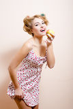 Portrait de la fille de pin-up blonde attirante de jeune belle femme mangeant la pomme et charmant le sourire regardant l'apparei Photo libre de droits