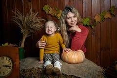 Portrait de la fille de sourire adorable posant avec le potiron orange dans l'intérieur en bois de chute fine Photographie stock