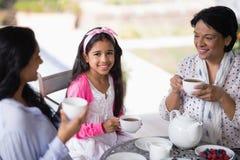 Portrait de la fille de sourire prenant le petit déjeuner avec la mère et la grand-mère Image stock