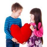 Portrait de la fille et du garçon tenant un grand oreiller en forme de coeur rouge Photographie stock libre de droits
