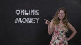 Portrait de la fille heureuse sur le fond noir appréciant des transferts d'argent en ligne banque de vidéos