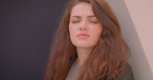 Portrait de la fille sérieuse de brune observant dans la caméra étant extérieur calme et rêveur sur le blck et le fond blanc banque de vidéos
