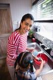 Portrait de la fille se tenante prêt de jeune mère travaillant dans la cuisine photos stock