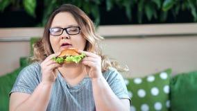 Portrait de la grosse femme de poids excessif de sourire heureuse mangeant l'hamburger appétissant regardant la caméra banque de vidéos