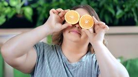 Portrait de la grosse femme suivante un régime drôle posant avec le plan rapproché moyen de demi yeux oranges de bâche banque de vidéos