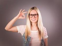 Portrait de la jeune belle femme blonde qui montrant à ` de signe le ` frais et souriant sur le fond gris Images libres de droits