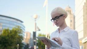 Portrait de la jeune belle femme d'affaires à l'aide de la tablette dehors Image libre de droits