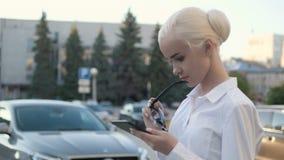 Portrait de la jeune belle femme d'affaires à l'aide de la tablette dehors Image stock