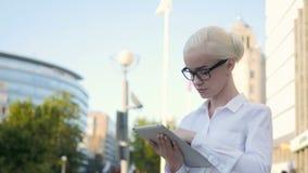 Portrait de la jeune belle femme d'affaires à l'aide de la tablette dehors Photos stock