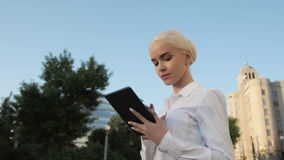 Portrait de la jeune belle femme d'affaires à l'aide de la tablette dehors Photos libres de droits