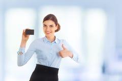 Portrait de la jeune belle femme d'affaires de sourire heureuse montrant quelque chose sur la carte ou le copyspase vide pour le  Image stock