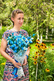 Portrait de la jeune belle femme de sourire avec de longs cheveux et fleurs dehors Photo stock