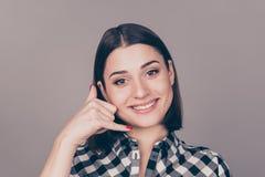 Portrait de la jeune belle femme me faisant à un appel signe avec elle photo stock