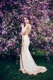 Portrait de la jeune belle femme posant parmi des arbres de fleur de ressort Images libres de droits