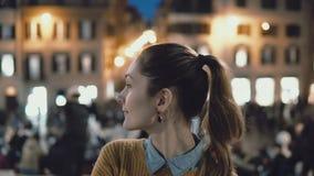 Portrait de la jeune belle femme se tenant au centre de la ville dans la soirée La fille d'étudiant regarde l'appareil-photo, sou banque de vidéos