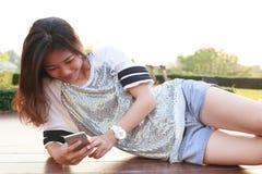 Portrait de la jeune belle femme se trouvant et lisant le texte sur smar Photographie stock
