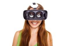 Portrait de la jeune belle fille de sourire heureuse obtenant l'expérience utilisant des verres de VR-casque de réalité virtuelle Photos stock