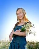 Portrait de la jeune blonde avec un bouquet des fleurs sauvages contre le ciel bleu Photographie stock