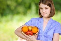 Portrait de la jeune brune de sourire tenant le panier avec des fruits Photos libres de droits