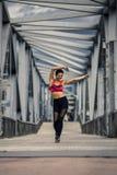 Portrait de la jeune et sportive femme dans les vêtements de sport marchant le long du pont Image libre de droits
