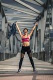 Portrait de la jeune et sportive femme dans les vêtements de sport marchant le long du pont Image stock