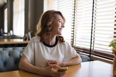 Portrait de la jeune femelle heureuse tenant un téléphone portable et regardant la fenêtre avec le sourire lumineux photo stock