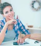 Portrait de la jeune femme à l'aide du téléphone portable tout en prenant le petit déjeuner dans la cuisine à la maison Photos libres de droits