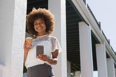Portrait de la jeune femme à l'aide du téléphone portable tout en tenant la tasse jetable Images libres de droits