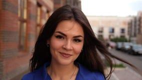 Portrait de la jeune femme élégante de brune marchant les rues de la femme caucasienne attirante de ville portant un manteau bleu banque de vidéos