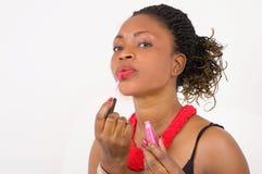 Portrait de la jeune femme africaine mettant le rouge à lèvres photos libres de droits